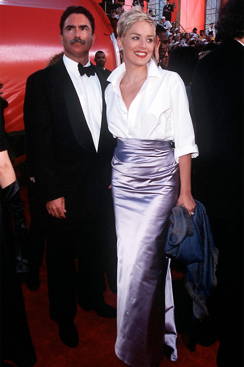 Áo sơ mi trắng mở cúc đầy phóng khoáng của Gap diện cùng chân váy Very Wang mang đến diện mạo trẻ trung và cá tính hút hồn cho mỹ nhân màn ảnh Sharon Stone trên thảm đỏ Oscar 1998