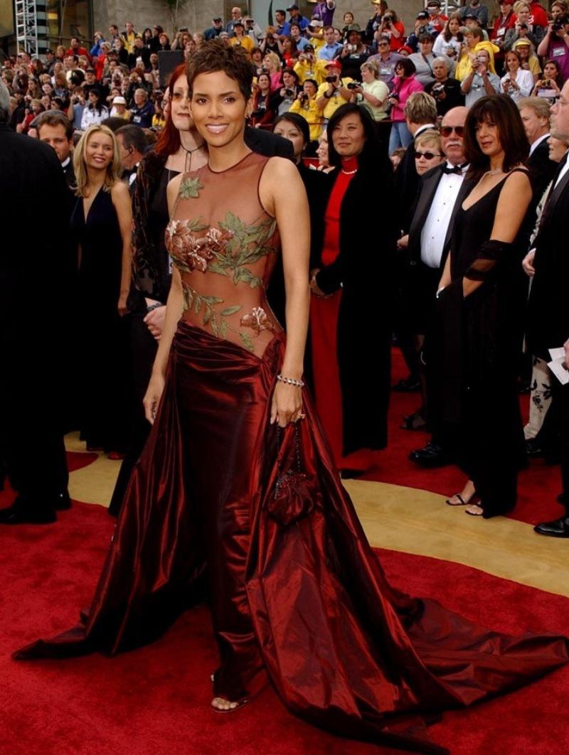 """Dáng vóc mỹ miều của nàng Halle Berry càng thêm phần hấp dẫn khi khoác trên mình chiếc đầm đỏ phối sheer nổi bật từ nhà mốt Elie Saab, xứng danh với giải thưởng """"Nữ diễn chính xuất sắc nhất"""" cho vai chính trong phim """"Monster's Ball"""" tại Oscar 2002"""
