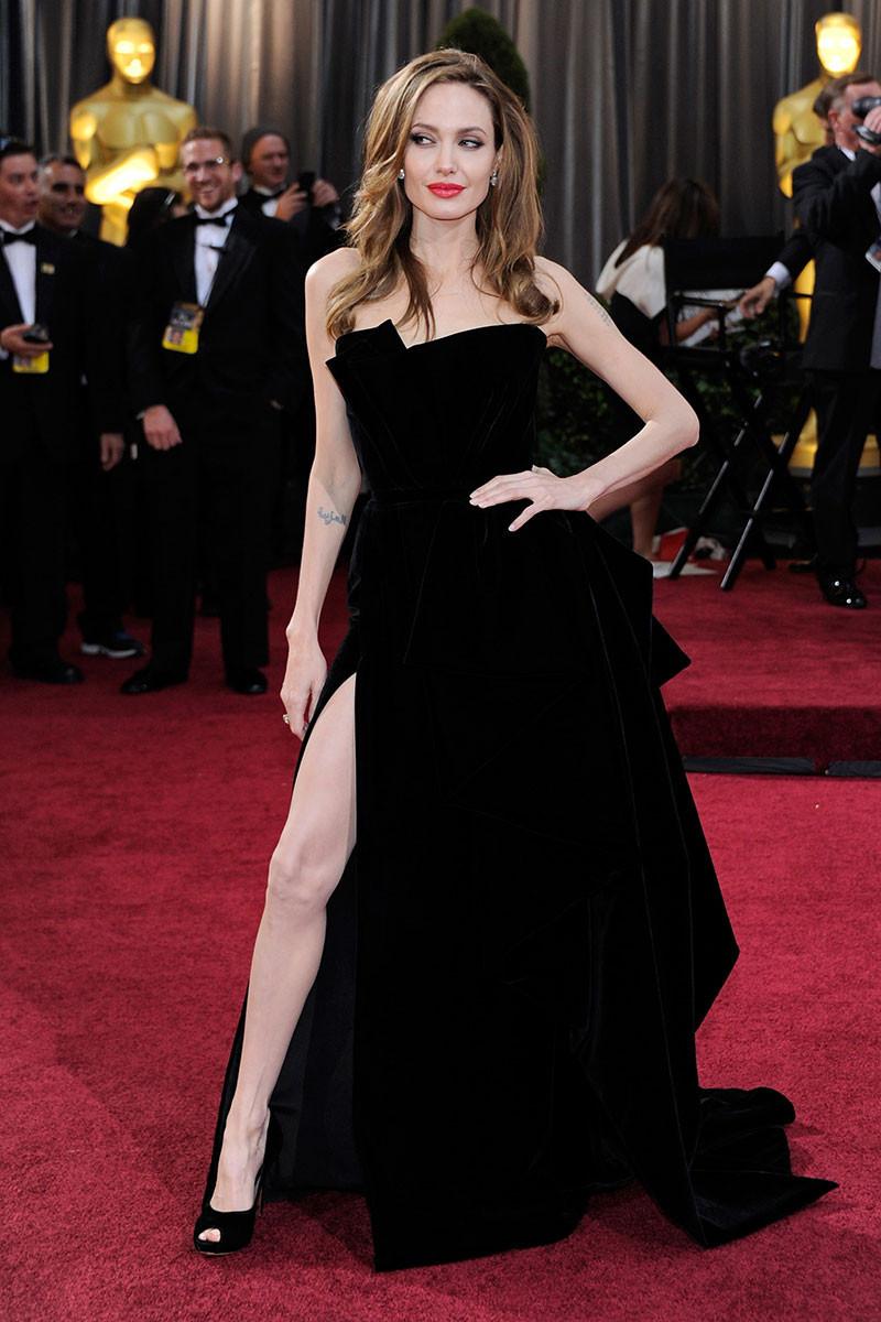 """Angelina Jolie tiếp tục là cái tên mặc đẹp nhất thảm đỏ Oscar 2012 trong thiết kế đầm nhung xẻ tà cao vút, một tuyệt phẩm được """"thổi hồn"""" bởi bàn tay tài hoa của nhà mốt Ý Atelier Versace"""