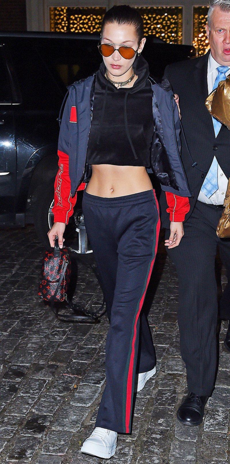 Bella Hadid tự tin khoe dáng chuẩn eo thon với áo crop-top, quần thể thao và áo khoác phối sọc đỏ được kết hợp vô cùng tinh tế