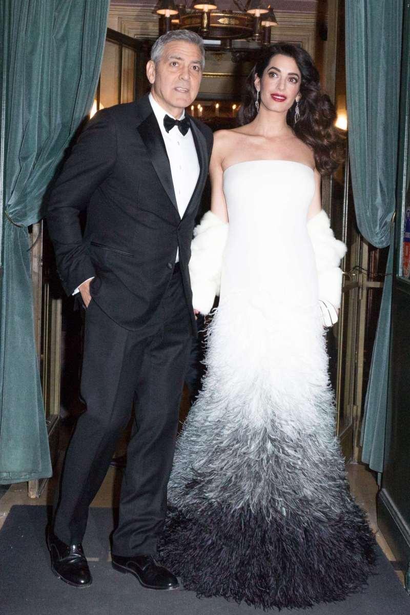 """Cesar Awards 2017 diễn ra ngày 24/2 là sự kiện đầu tiên cặp đôi quyền lực xuất hiện trước công chúng sau khi công bố tin vui song thai. Amal Clooney e ấp bên chồng trong bộ đầm trắng cup ngực phối lông tuyệt đẹp được """"thổi hồn"""" bởi nhà mốt Atelier Versace"""
