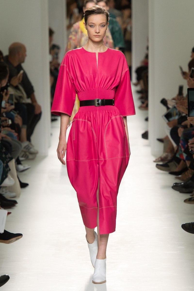 Cũng là thiết kế đầm dài quá gối nhưng Hermès lại mang đến cảm giác mạnh mẽ và quyền lực với gam hồng fuchsia nóng bỏng cùng những đường cắt xẻ sắc sảo, phóng khoáng