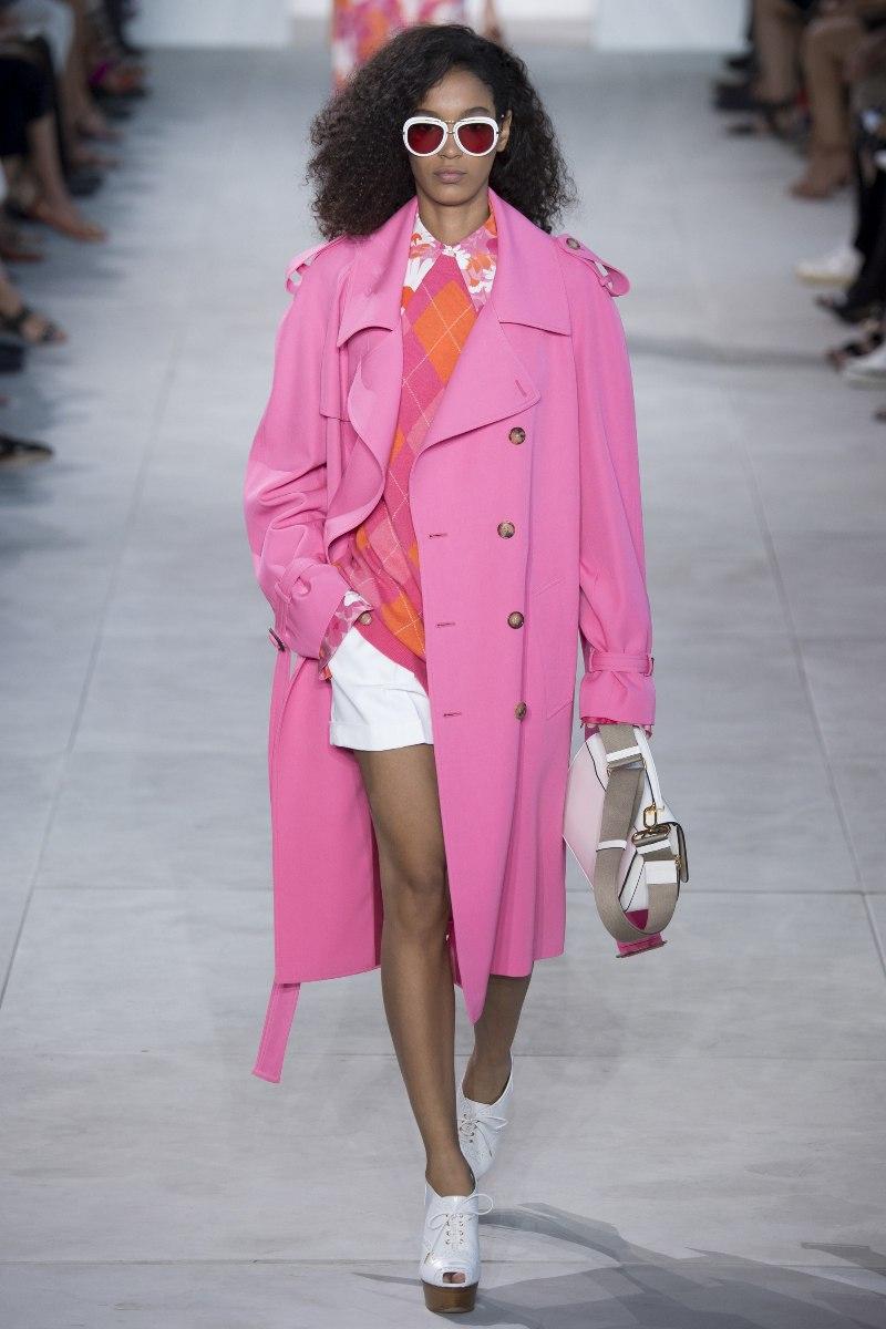 """Nhà mốt Michael Kors chứng tỏ đẳng cấp """"chơi màu"""" thú vị với điểm nhấn là áo khoác dáng dài màu hồng kẹo gum ngọt ngào, thêm phần phong cách với quần short và loạt phụ kiện mang sắc trắng sành điệu"""