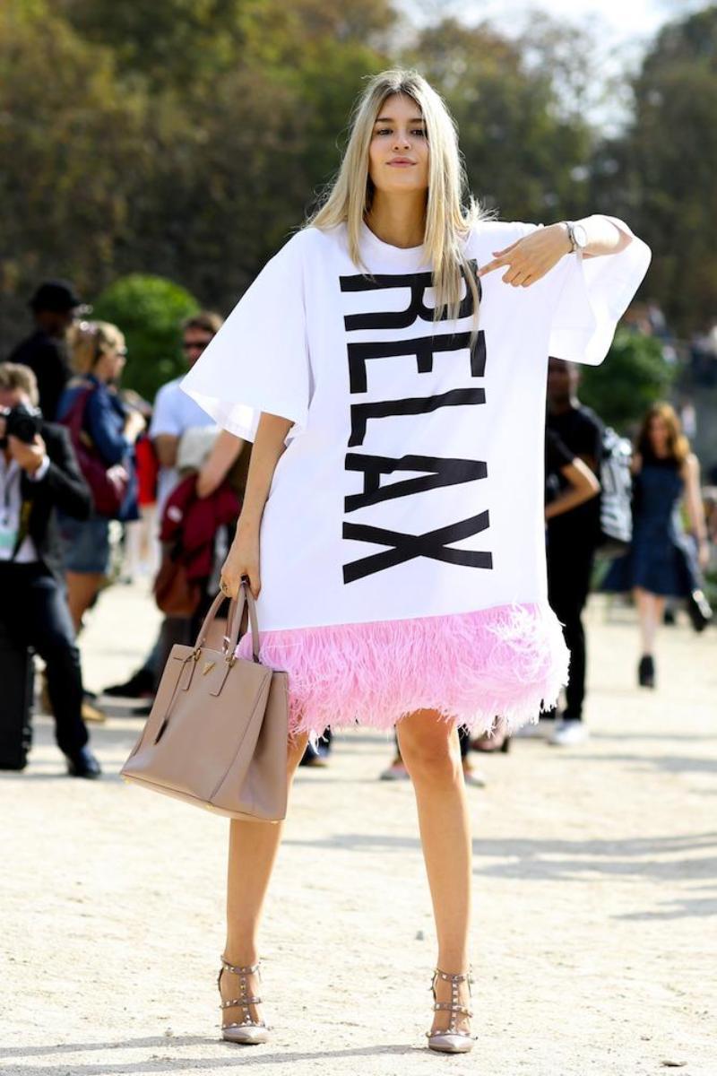 Sắc hồng ngọt ngào của lông vũ nâng tầm thiết kế váy trắng in chữ kinh điển, biến chúng trở thành món đồ đáng thèm muốn của mọi tín đồ thời trang