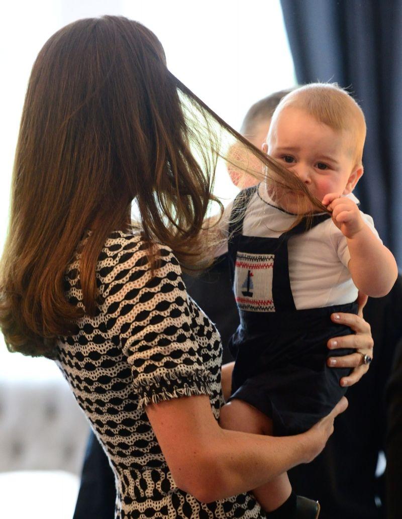 Hoàng tử George nghịch tóc mẹ. Cậu bé bị bố William ví như... một chú khỉ con vì quá hiếu động.