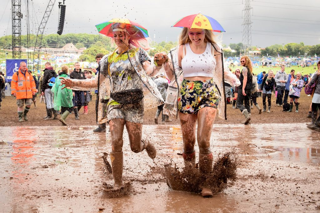 "Revellers run through a puddle as they pose for photographers, on the first official day of the Glastonbury Festival of Music and Performing Arts on Worthy Farm in Somerset, south west England, on June 27, 2014. US metal giants Metallica will play this year's coveted Saturday night headline spot at Britain's Glastonbury festival, organisers announced Thursday. It will be the ""Master of Puppets"" four-piece's first appearance at the legendary festival, held in south west England, following on from The Rolling Stones' Worthy Farm debut last year. AFP PHOTO / LEON NEAL Click here to display all information about this document. (Photo credit should read LEON NEAL/AFP/Getty Images)"