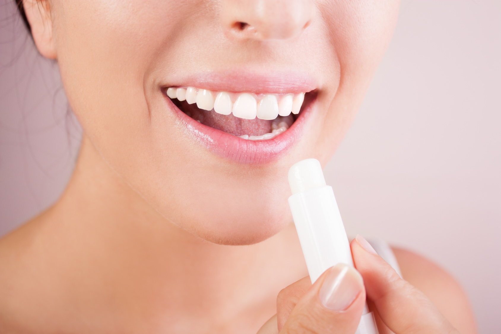 Lips care.woman applying balsam on lips