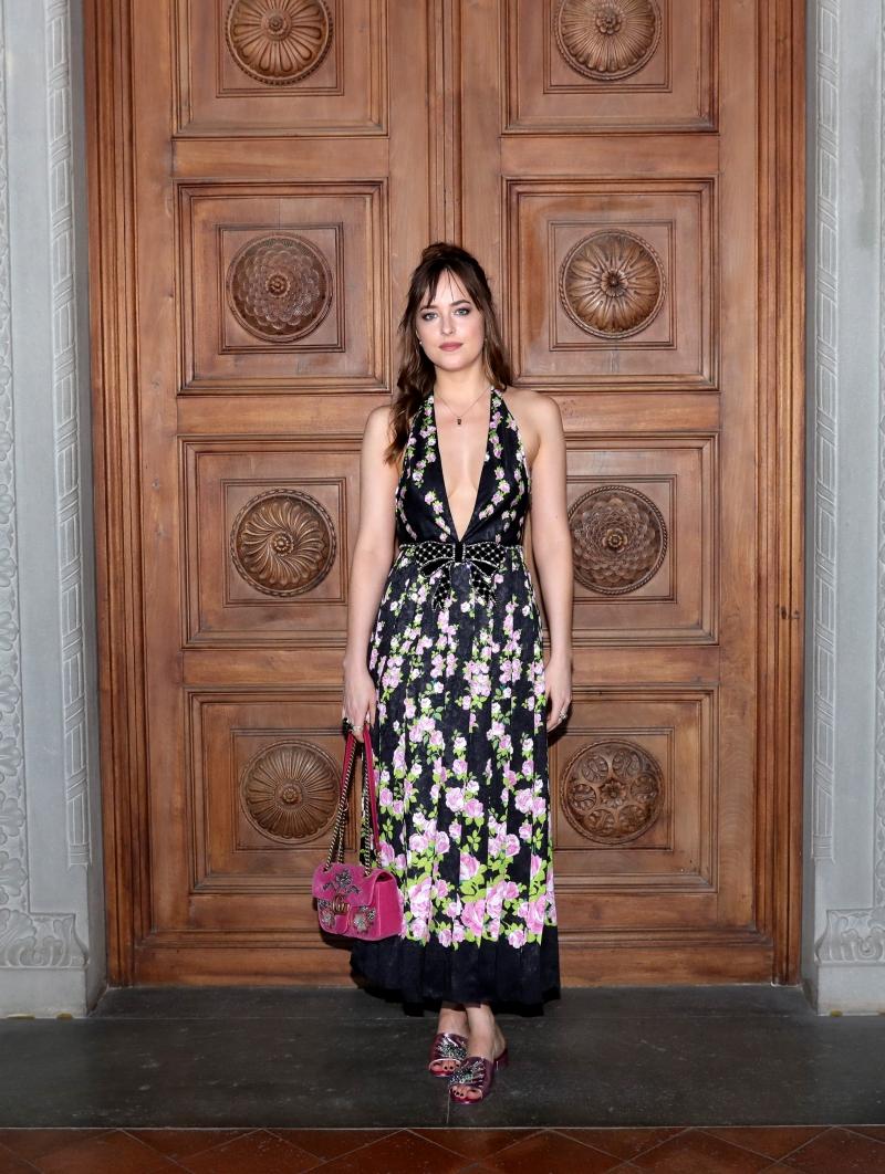 Nữ diễn viên Dakota Johnson mặc một thiết kế đầm in hoa có cổ xẻ sâu gợi cảm phối cùng túi xách GG Marmont bằng nhung