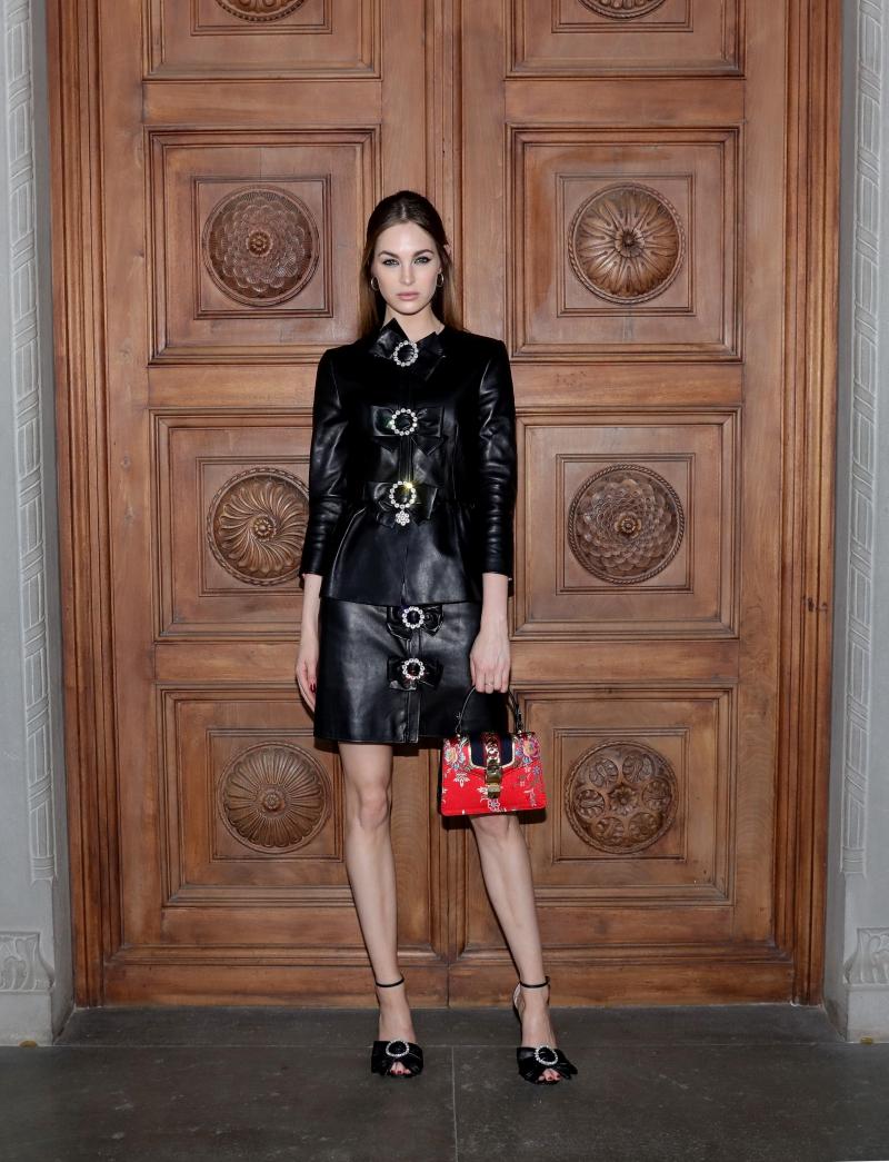 """Cô nàng Laura Love mặc nguyên """"cây"""" màu đen trong BST Chớm Thu 2017 của Gucci. Cô chọn phụ kiện là túi xách Sylvie bằng gấm tạo điểm nhấn cho tổng thể trang phục."""