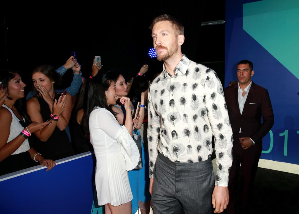 DJ Calvin Harris chọn áo sơ mi in họa tiết lông công và quần tây lịch lãm.