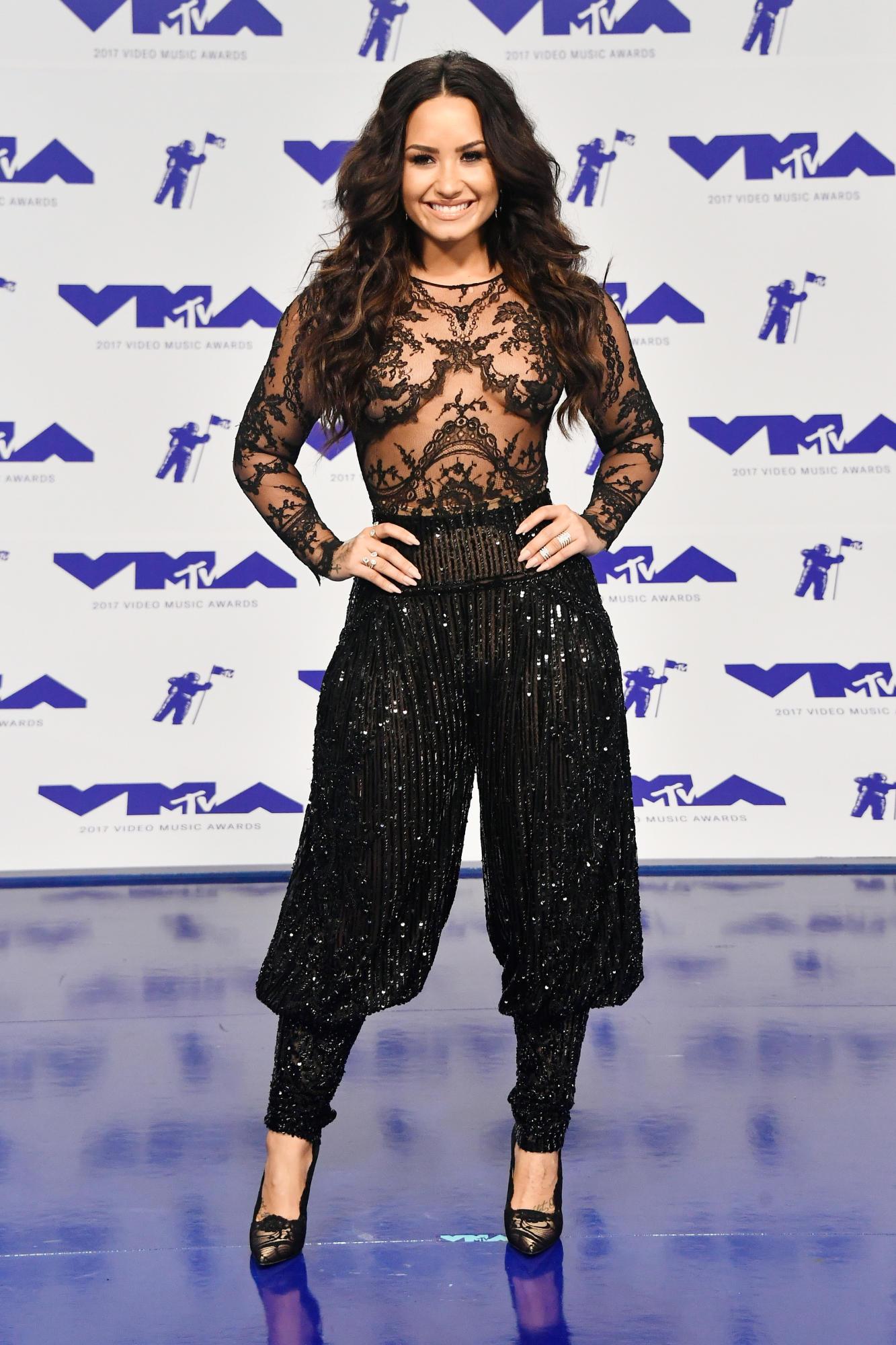 """Demi Lovato với bộ trang phục đen tuyền của Zuhair Murad vô cùng gợi cảm và tinh tế. Áo dài tay gần như """"naked"""" với những họa tiết thêu đính đối xứng tinh xảo phối cùng quần harem đính kim sa vừa tôn được vẻ quyến rũ của Demi Lovato, vừa khắc phục được nhược điểm về chiều cao của cô."""