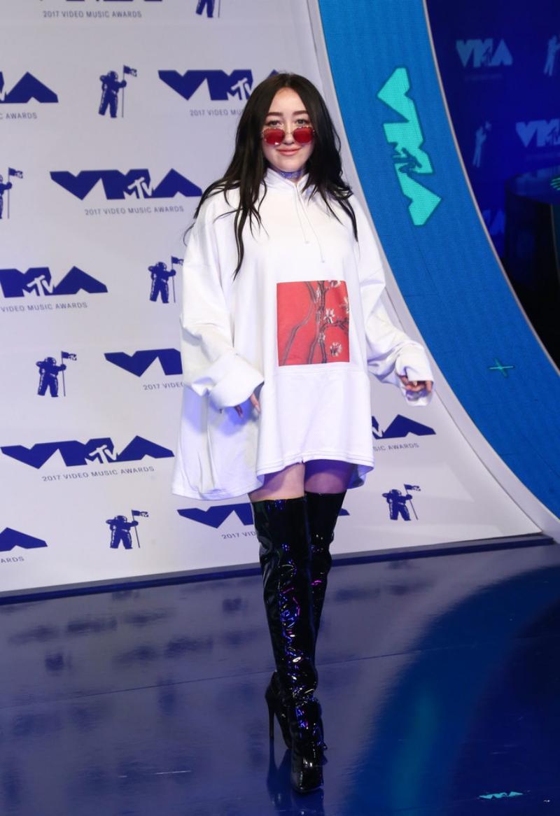 Noah Cyrus, em gái của Miley Cyrus, chọn mặc áo sweater quá khổ phối cùng boots da bóng cao cổ và cặp kính mắt màu thời thượng.