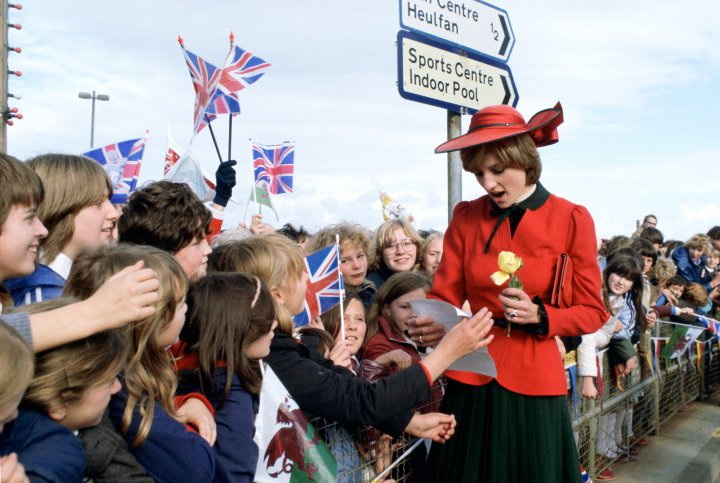 RHYL, UNITED KINGDOM - OCTOBER 27: Princess Diana In Rhyl On Her First Official Visit To Wales Is Greeted By A Huge Crowd Waving Union Jack Flags. Some Of The Children Wrote Notes And Poems Which She Read.her Outfit Designed By Donald Campbell (Photo by Tim Graham/Getty Images)