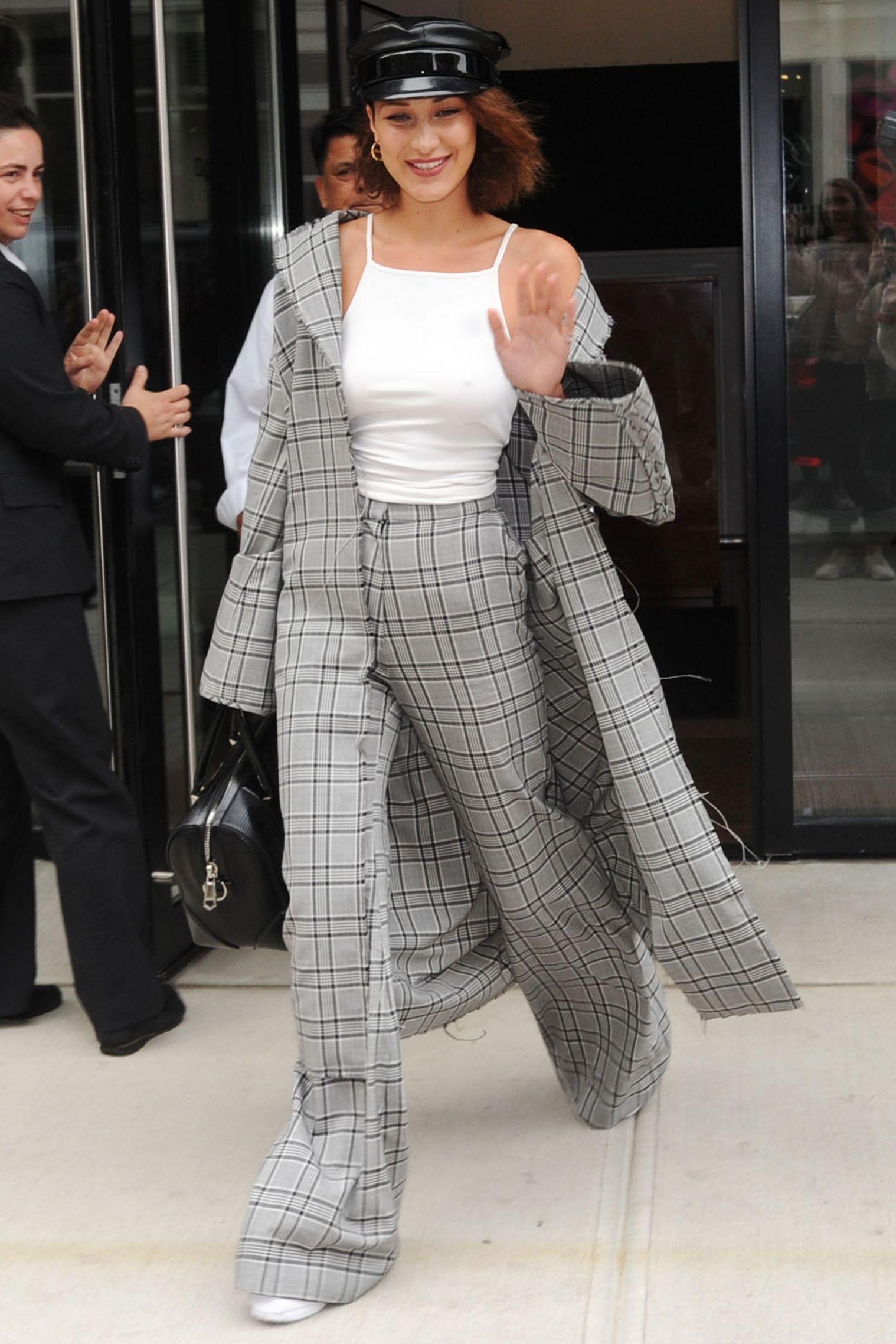 Chiếc mũ Chrome Hearts do chính Bella Hadid thiết kế được người mẫu sử dụng làm điểm nhấn cho bộ trang phục hoạ tiết kẻ tông màu trung tính.