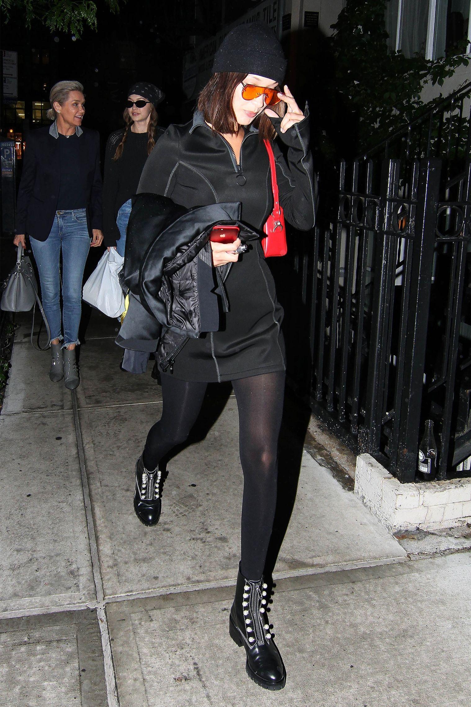 Mắt kính và túi xách màu nóng tạo nên sức cuốn hút đặc biệt cho set quần áo dạo phố đêm all-black của Bella.