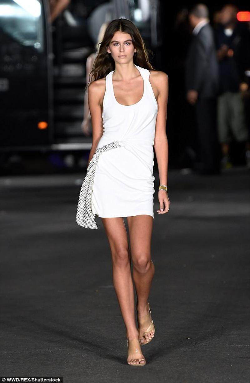 Trong show diễn BST Xuân Hè 2018 của NTK Alexander Wang, Kaia Gerber mặc một thiết kế đầm trắng với cổ khoét sâu và những chi tiết nhấn nhá khỏe khoắn. Sức hút của cô gái vừa tròn 16 tuổi quả thực đã khiến cho khán giả đứng ngồi không yên.