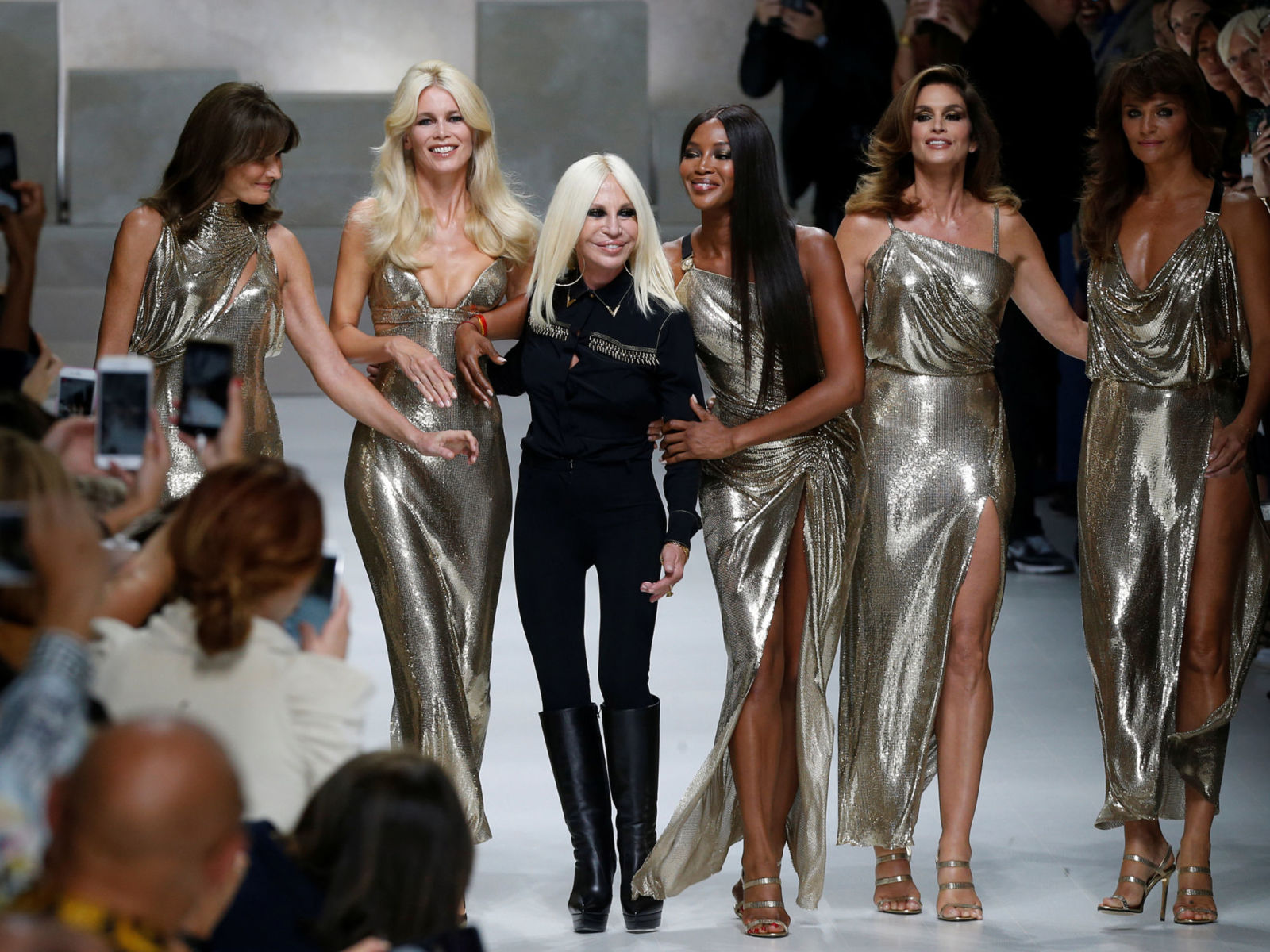 Italian designer Donatella Versace (3L) acknowledges the applause with former top models Carla Bruni (L), Claudia Schiffer, Naomi Campbell, Cindy Crawford and Helena Christensen (R) at the end of Versace Spring/Summer 2018 show at the Milan Fashion Week in Milan, Italy, September 22, 2017. REUTERS/Stefano Rellandini - RC14D32932B0