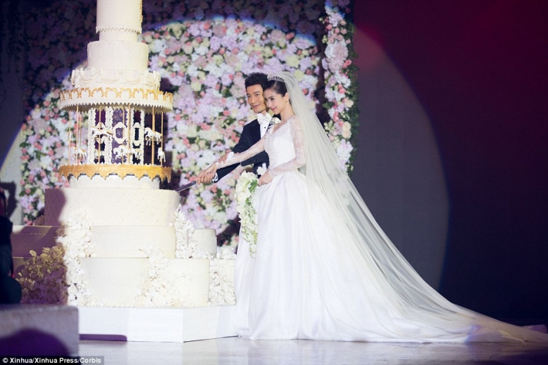 """Chiếc váy cưới của Angelababy được làm bằng lụa organza và satin trắng ngà, do đích thân cựu Giám đốc Sáng tạo Raf Simons thiết kế; và mất 5 tháng mới có thể hoàn thiện được đơn hàng """"đắt giá"""" này."""