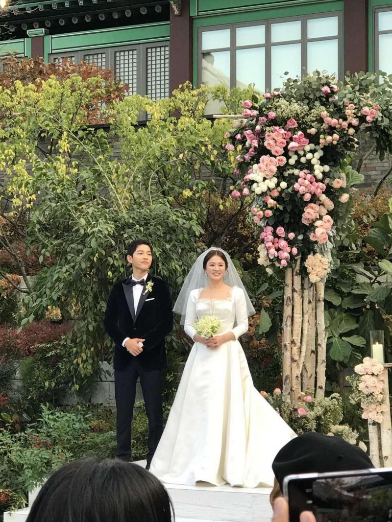 Cô dâu tỏa sáng với niềm hạnh phúc trong thiết kế váy cưới của Dior bên cạnh chú rể lịch lãm.
