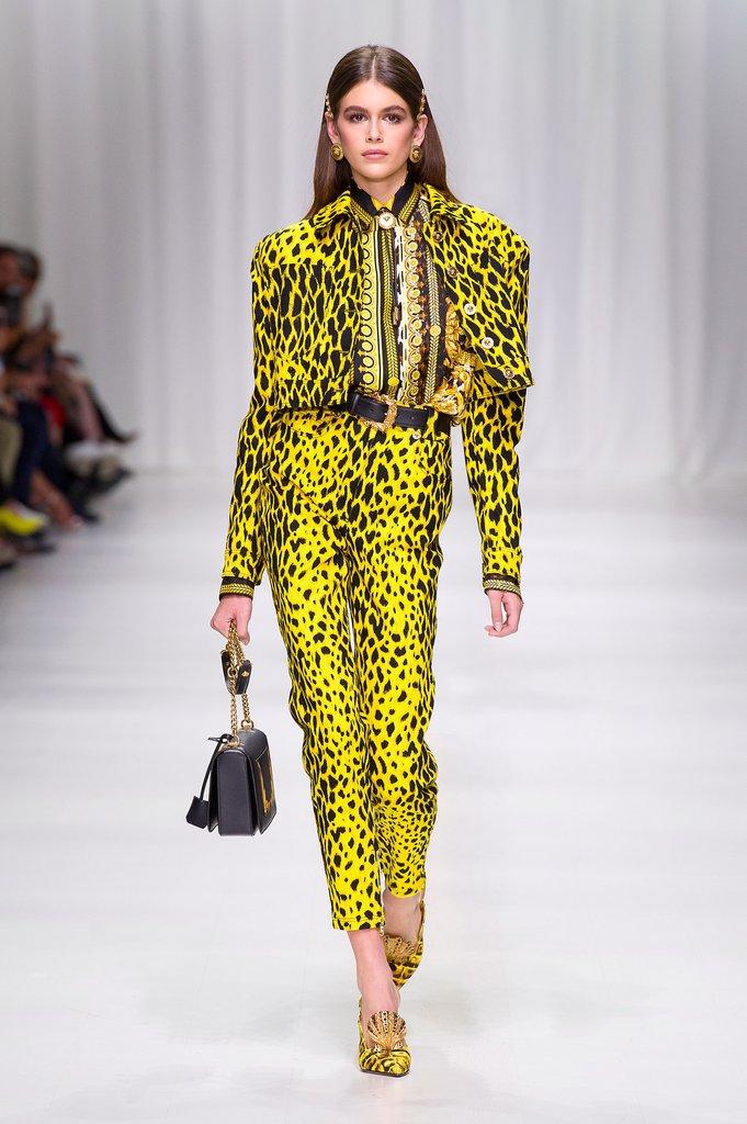 Kaia Gerber khoe đôi chân dài miên man trong thiết kế Xuân Hè 2018 của Versace. Mẹ cô, siêu mẫu Cindy Crawford, cũng xuất hiện trong show diễn đặc biệt kỷ niệm 20 năm ngày mất của nhà sáng lập Gianni Versace.
