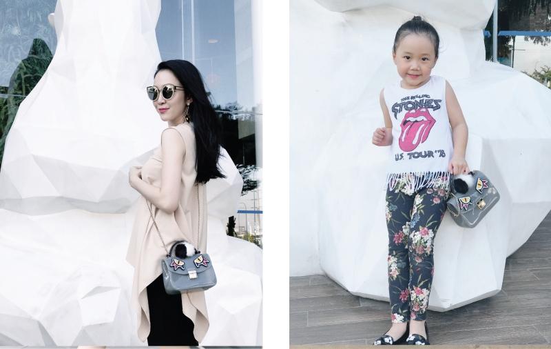 """Linh Nga vẫn luôn gắn liền với phong cách nữ tính ngay cả khi phối trang phục cùng quần trong khi bé Luna """"quậy"""" hơn hẳn với áo sát nách và quần in hoa. Cả hai mẹ con đều xách túi Furla Candy Jungle với các chi tiết trang trí ngộ nghĩnh."""