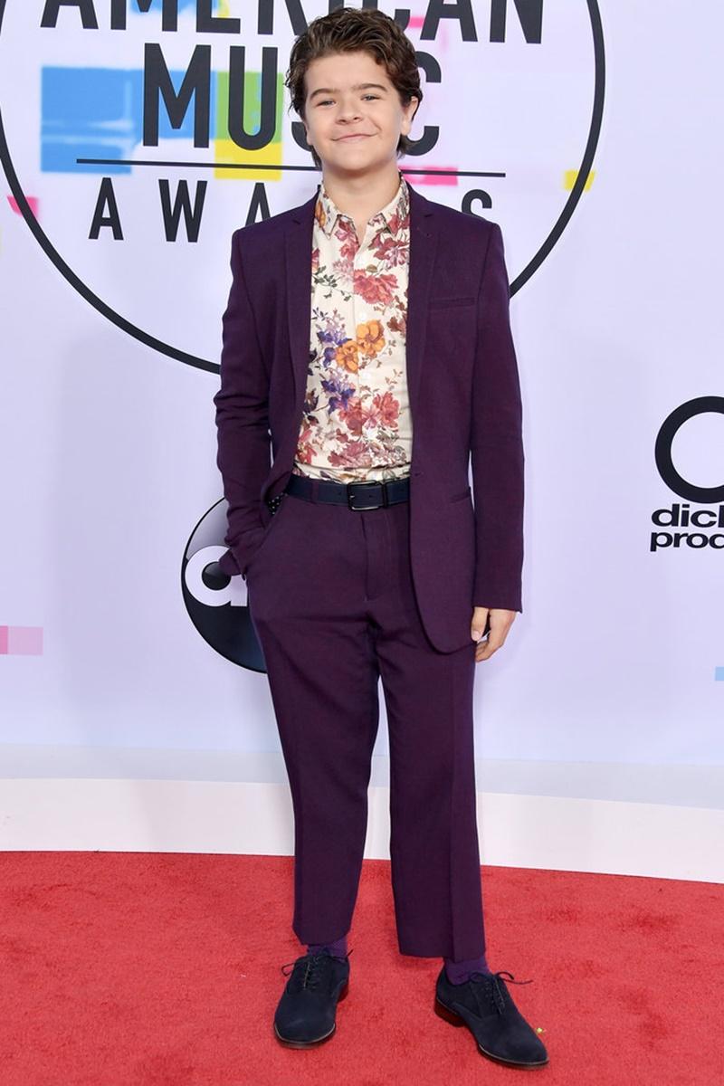 """Diễn viên Gaten Matarazzo trong phim 'Stranger Things"""" mặc bộ suit màu tím bảnh bao phối cùng áo sơ mi in họa tiết hoa bên trong. Cậu nhóc phối nguyên bộ trang phục của ASOS cùng giày Aldo."""
