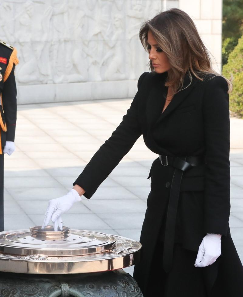Thăm viếng Nghĩa trang Quốc gia Seoul, Melania Trump mặc chiếc áo khoác màu đen của nhà mốt Alexander McQueen. Điểm nhấn của trang phục là chiếc thắt lưng được cài nút thắt gọn gàng.