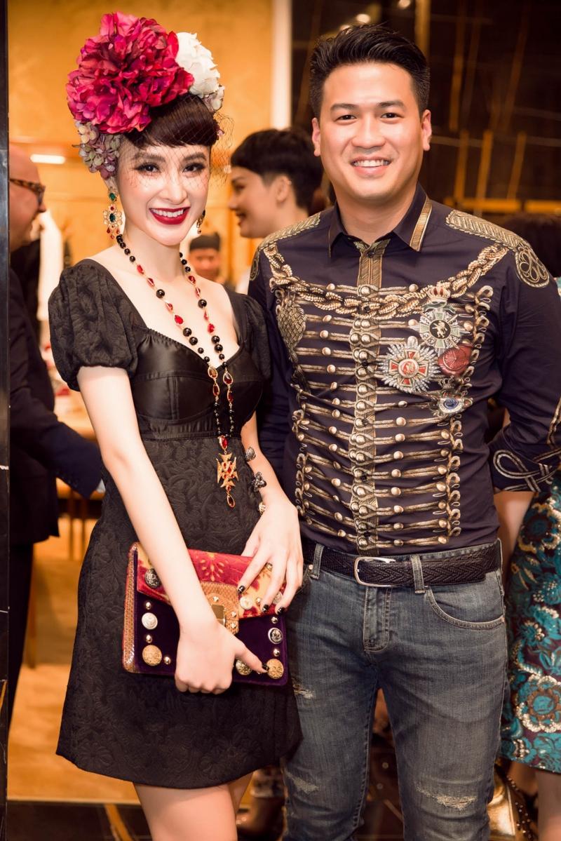 """Diễn viên Angela Phương Trinh """"chịu khó"""" đội hẳn một chiếc mũ cầu kỳ để tạo điểm nhấn cho tổng thể trang phục. Doanh nhân Phillip Nguyễn mặc áo sơ mi Dolce & Gabbana với họa tiết mô phỏng trang phục hoàng gia phối cùng quần jeans khỏe khoắn."""