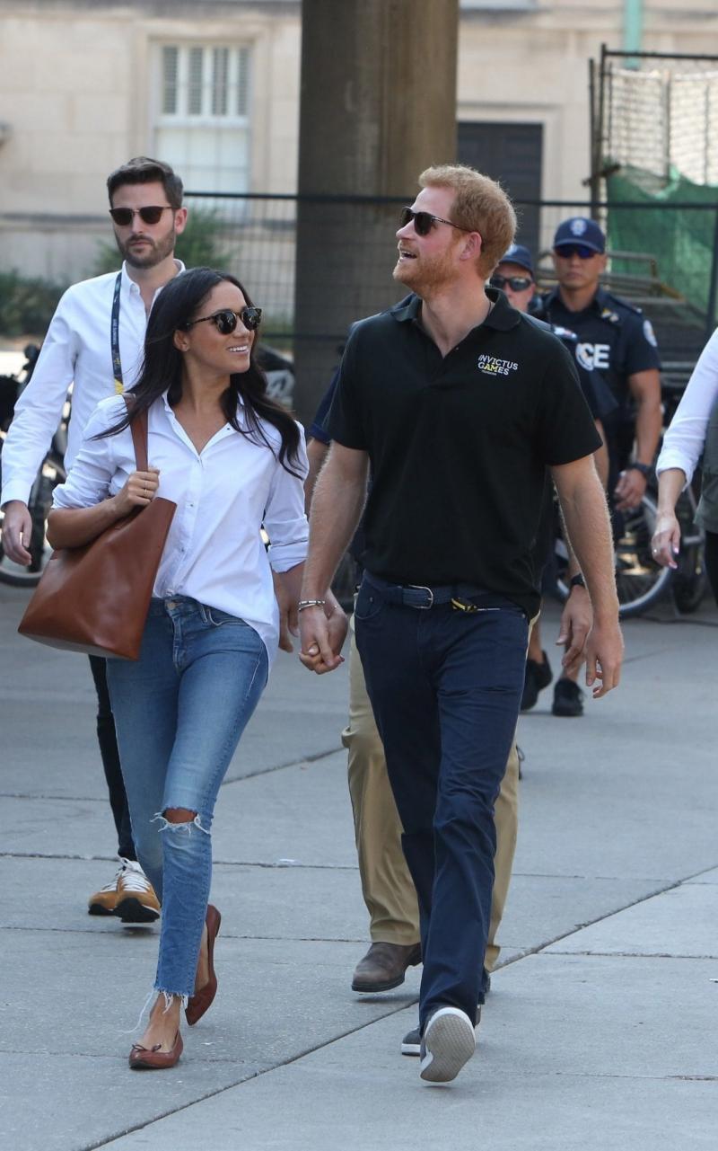 Xuất hiện cùng Hoàng tử Harry hồi tháng 10 vừa qua, Meghan Markle chọn cho mình bộ trang phục không thể đơn giản hơn: áo sơ mi trắng và quần jeans rách gấu.