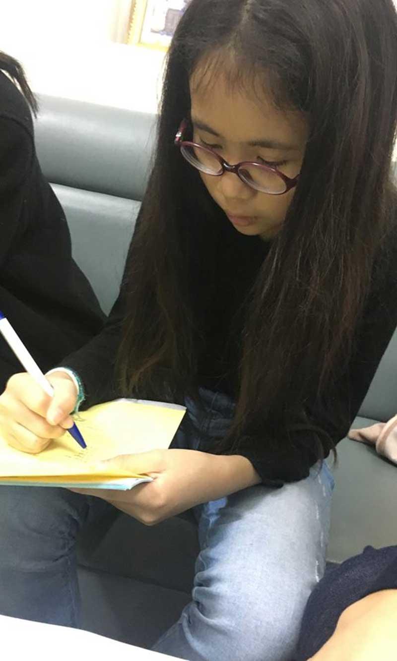 Cô gái bé nhỏ An Mi (11 tuổi) đang điền vào lá đơn xin hiến tạng tại Bệnh viện Việt Đức ngày 28/12.
