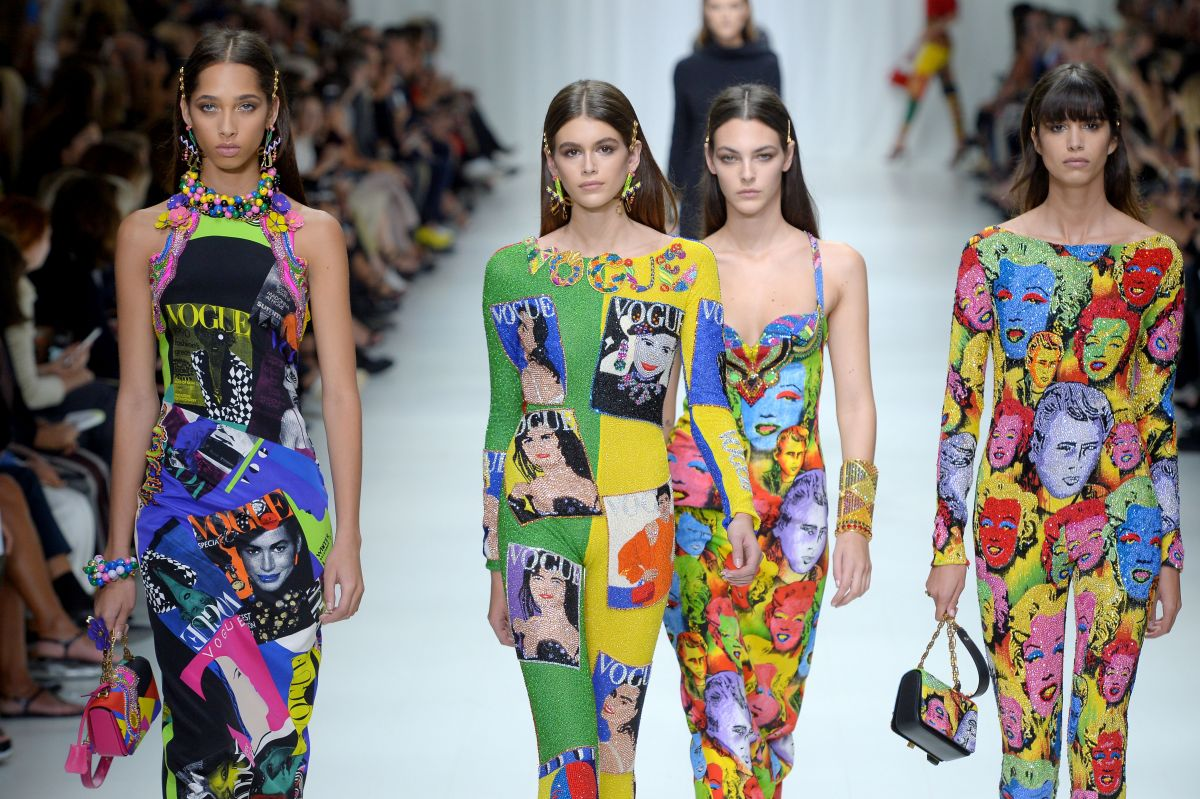 Cũng trong show diễn Xuân Hè 2018 của Versace, Kaia (thứ hai từ trái qua) mặc một thiết kế khác với họa tiết là các bìa tạp chí Vogue được xử lý màu theo phong cách pop-art.