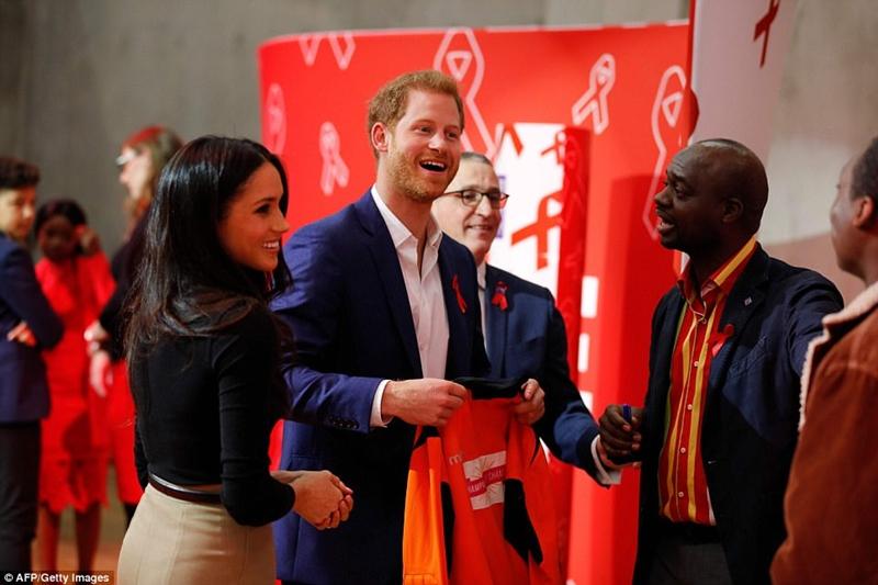 Harry và Meghan cười khi họ được trao một chiếc T-shirt bởi một tổ chức từ thiện gần với trái tim của hoàng tử