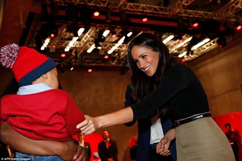Nữ diễn viên người Mỹ Meghan Markle nói chuyện với một cậu bé khi họ tham quan hội chợ từ thiện Terrence Higgins Trust World AIDS Day của Terrence Higgins