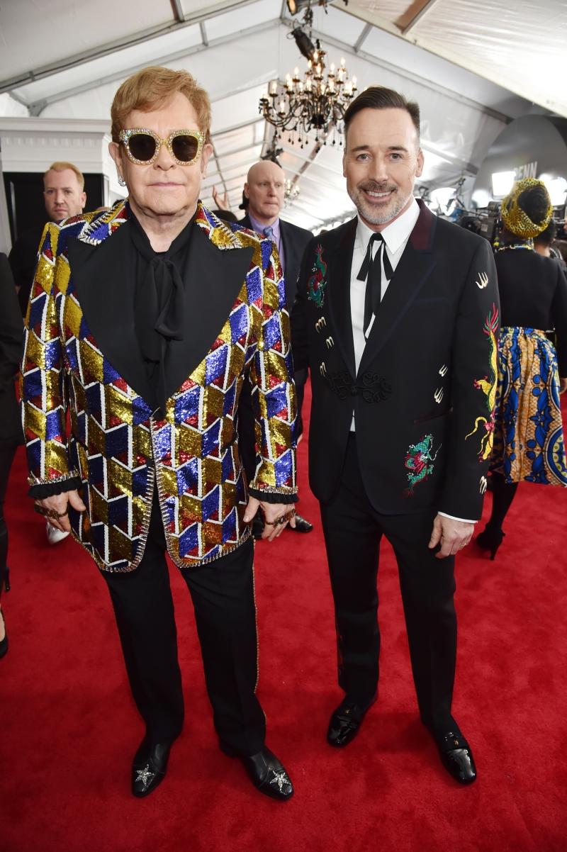 """Elton John (trái) và bạn đời David Furnish mặc trang phục """"hàng thửa"""" từ thương hiệu Gucci. Sắp tới trong tour lưu diễn vòng quanh thế giới kéo dài trong 3 năm của Elton John, Gucci cũng hân hạnh """"đồng hành"""" với những bộ trang phục đặc sắc cho nam danh ca lừng lẫy người Anh này."""