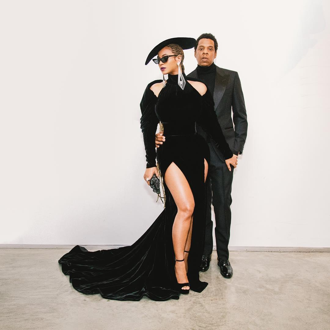 """Mặc dù """"tay xách nách mang"""" phải giữ đồ ăn và đồ uống cho cô con gái rượu nhưng hai vợ chồng Beyonce và Jay-Z cũng tranh thủ được những khoảnh khắc tạo dáng riêng. Beyonce mặc đầm Nicolas Jebran cùng với mũ rộng vành cùng thương hiệu. Jay-Z mặc suit với áo cổ lọ của Tom Ford."""