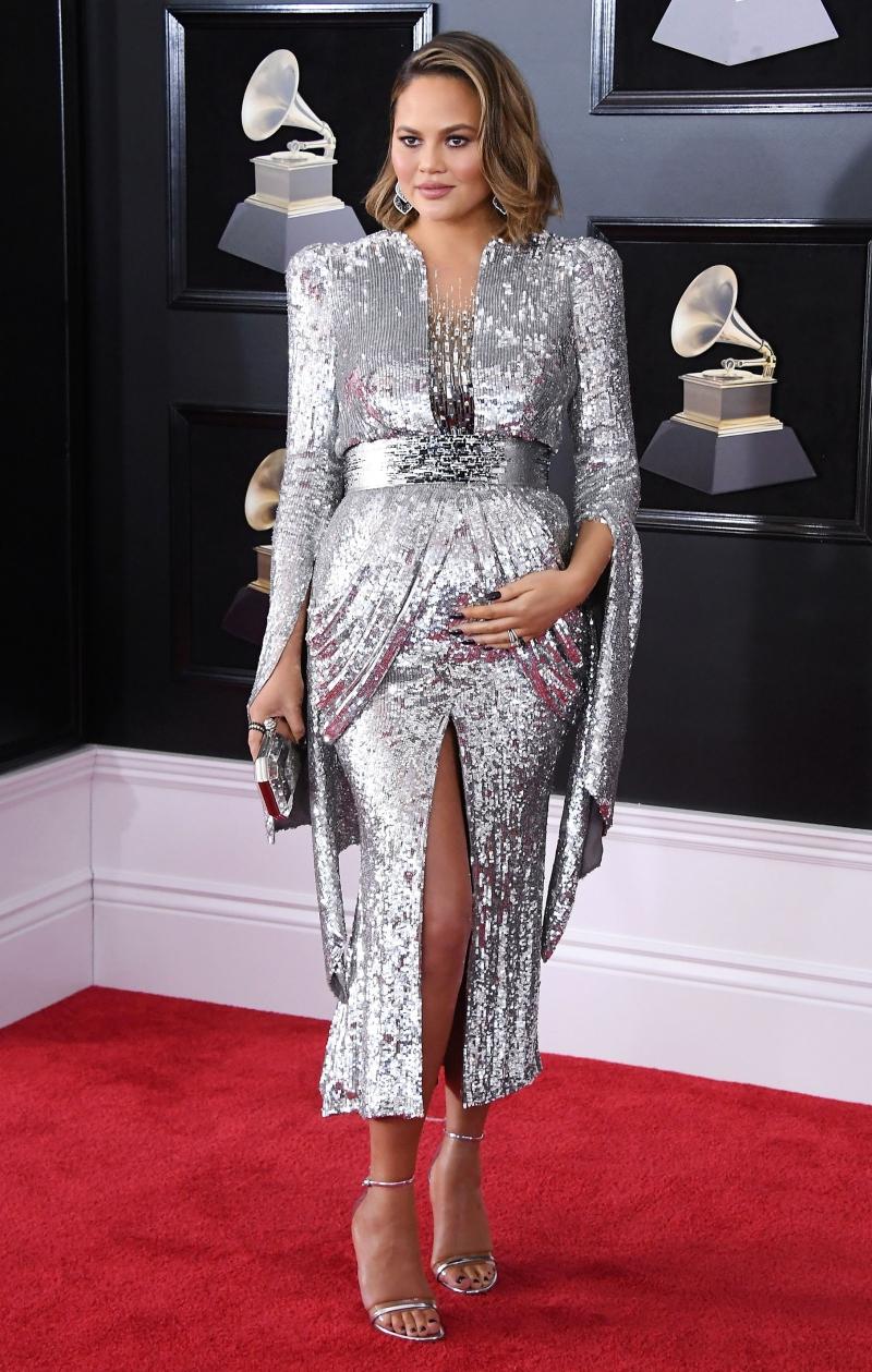 Chrissy Teigen rạng rỡ khoe bụng bầu trong thiết kế đầm ánh kim lấp lánh với những đường cắt xẻ gợi cảm của Yanina Couture cùng với trang sức của Lorraine Schwartz.