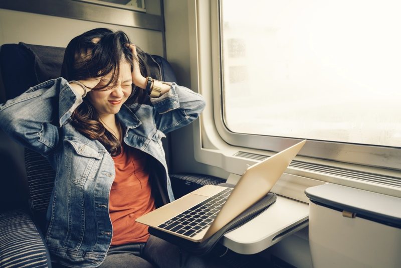 Asian college girl frustrated with laptop on the train
