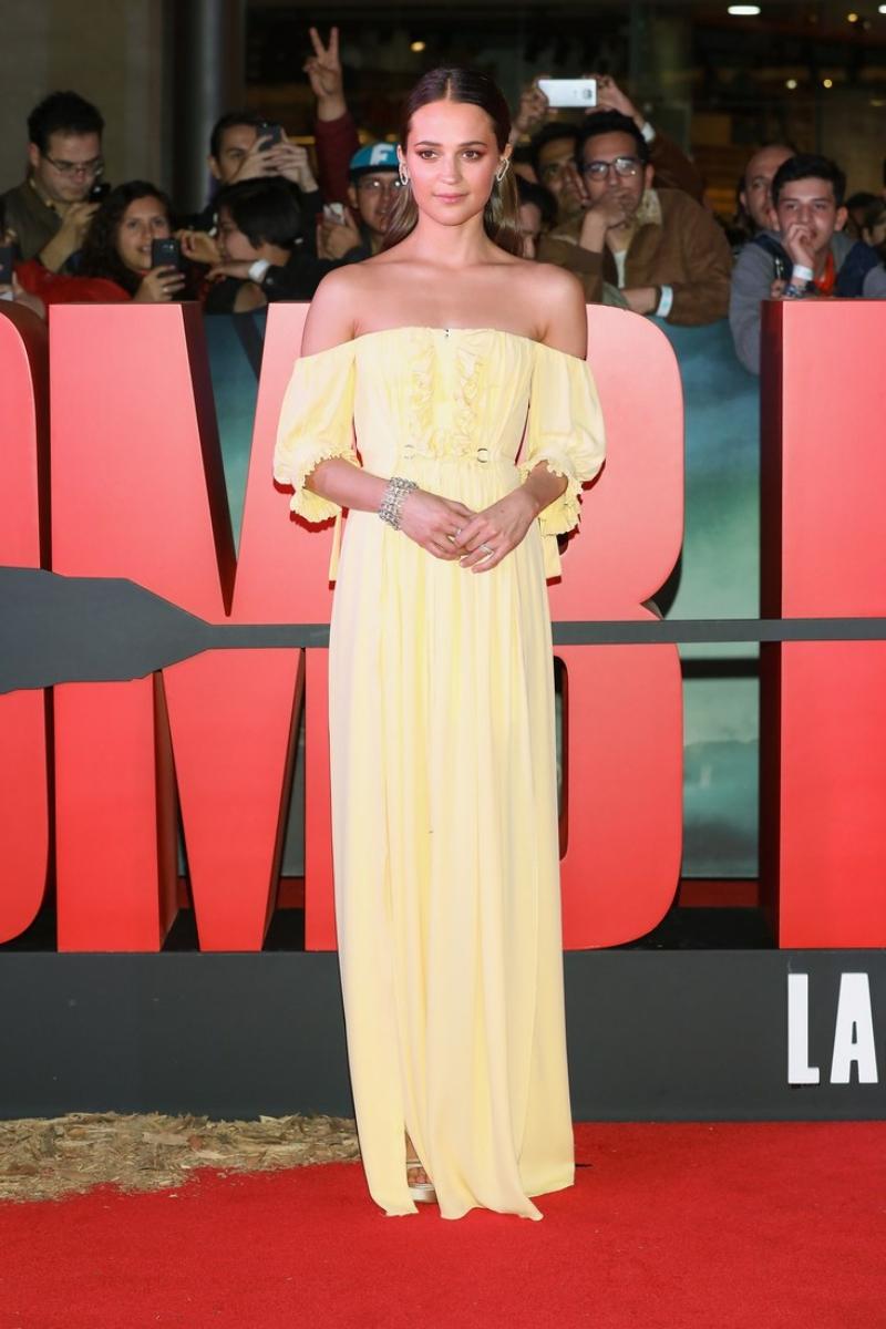 """Đến Mexico, Alicia Vikander chọn một thiết kế đầm trễ vai cũng của Louis Vuitton với tông màu vàng nhạt. """"Vũ khí"""" của cô trên thảm đỏ vẫn là những món nữ trang với thiết kế bắt mắt, tạo điểm nhấn hoàn hảo cho tổng thể trang phục."""
