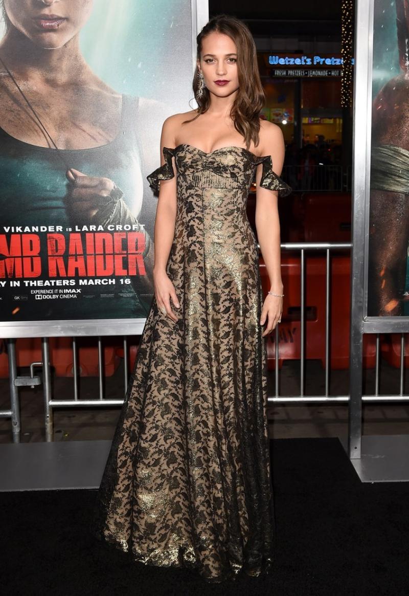 Trong buổi ra mắt phim tại Hollywood, Alicia Vikander quyến rũ tuyệt đối với thiết kế đầm trễ vai dệt sợi ánh kim cùng gương mặt được trang điểm đậm hơn. Mái tóc được tạo kiểu lệch sang một bên để lộ ra thiết kế khuyên tai độc đáo.