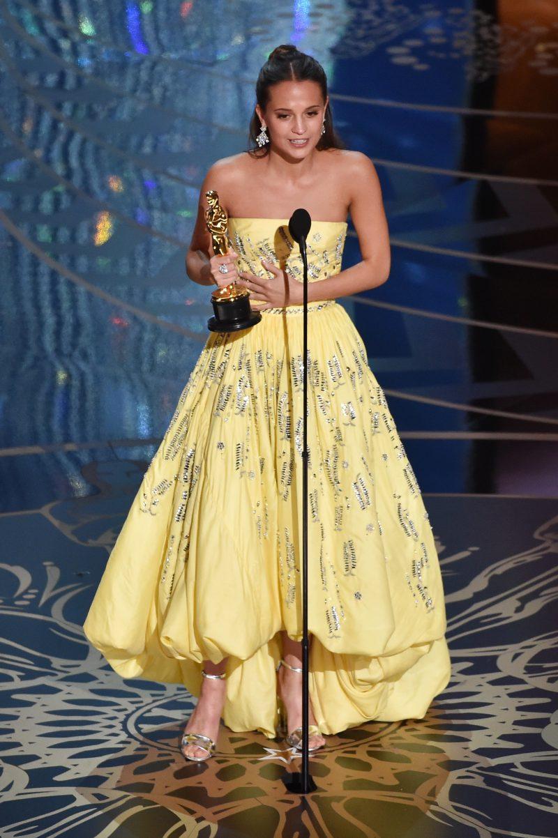 """Một trong những bộ váy quan trọng của Louis Vuitton thực hiện cho Alicia Vikander là thiết kế đầm hở vai màu vàng dệt sợi ánh kim tại Oscar năm 2016, khi cô lên nhận giải Nữ diễn viên phụ xuất sắc nhất cho vai diễn trong """"The Danish Girl""""."""