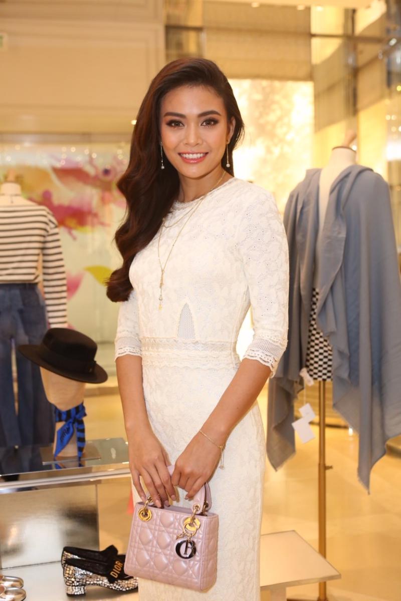 Tân Á hậu Hoàn vũ Mâu Thủy nhẹ nhàng và nữ tính trong một thiết kế đầm trắng tinh khôi. Cô xách túi Lady Dior nhỏ xinh màu hồng nhẹ nhàng.