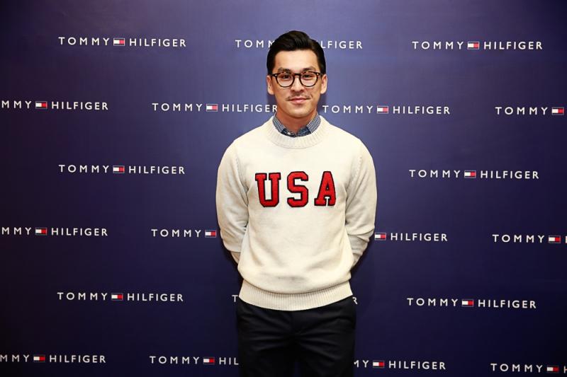 Nhiếp ảnh gia Thiên Minh trong một thiết kế sweater với dòng chữ USA mang phong cách preppy trẻ trung của Tommy Hilfiger.