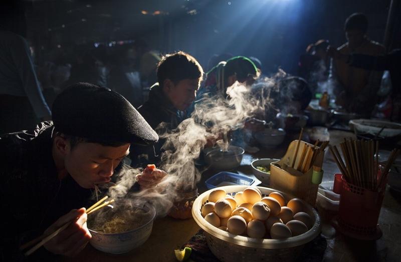 """Chia sẻ về cảm hứng của bức ảnh, tác giả cho biết:""""Ở miền bắc Việt Nam, mọi người thường tới các phiên chợ để trao đổi hàng hóa và văn hóa. Họ thường dậy rất sớm để đi chợ và ăn sáng tại đây""""."""