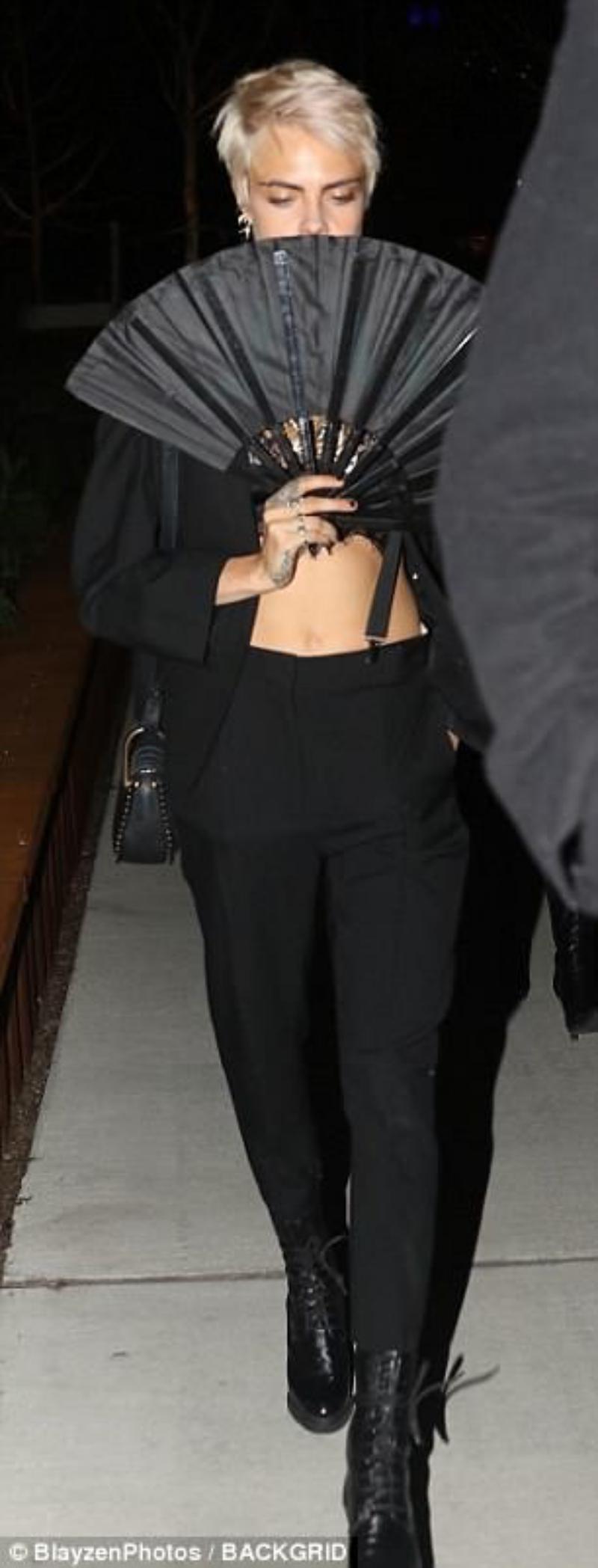Cara Delevingne mặc nguyên cây màu đen cùng phụ kiện là chiếc quạt để... che mặt.