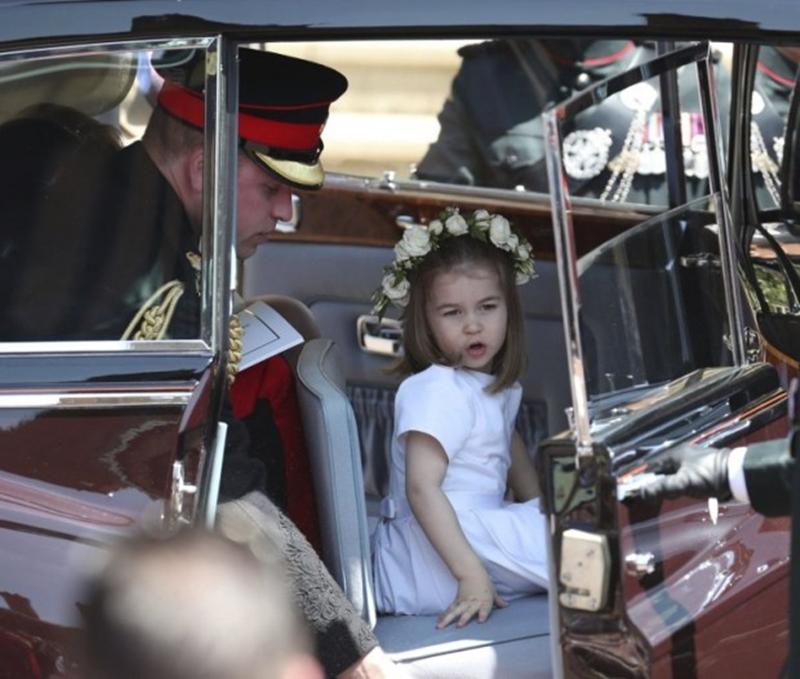 cô em hiếu động thì anh trai, Hoàng tử George, lại ngại ngùng, nấp sau lưng cha trong một bức ảnh chụp trước cổng nhà nguyệ