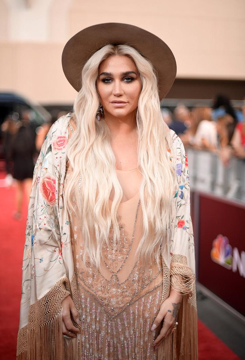 Kesha chọn cho mình phong cách du mục với áo choàng dài với những sợi tua rua cùng phụ kiện là mũ vành rộng.