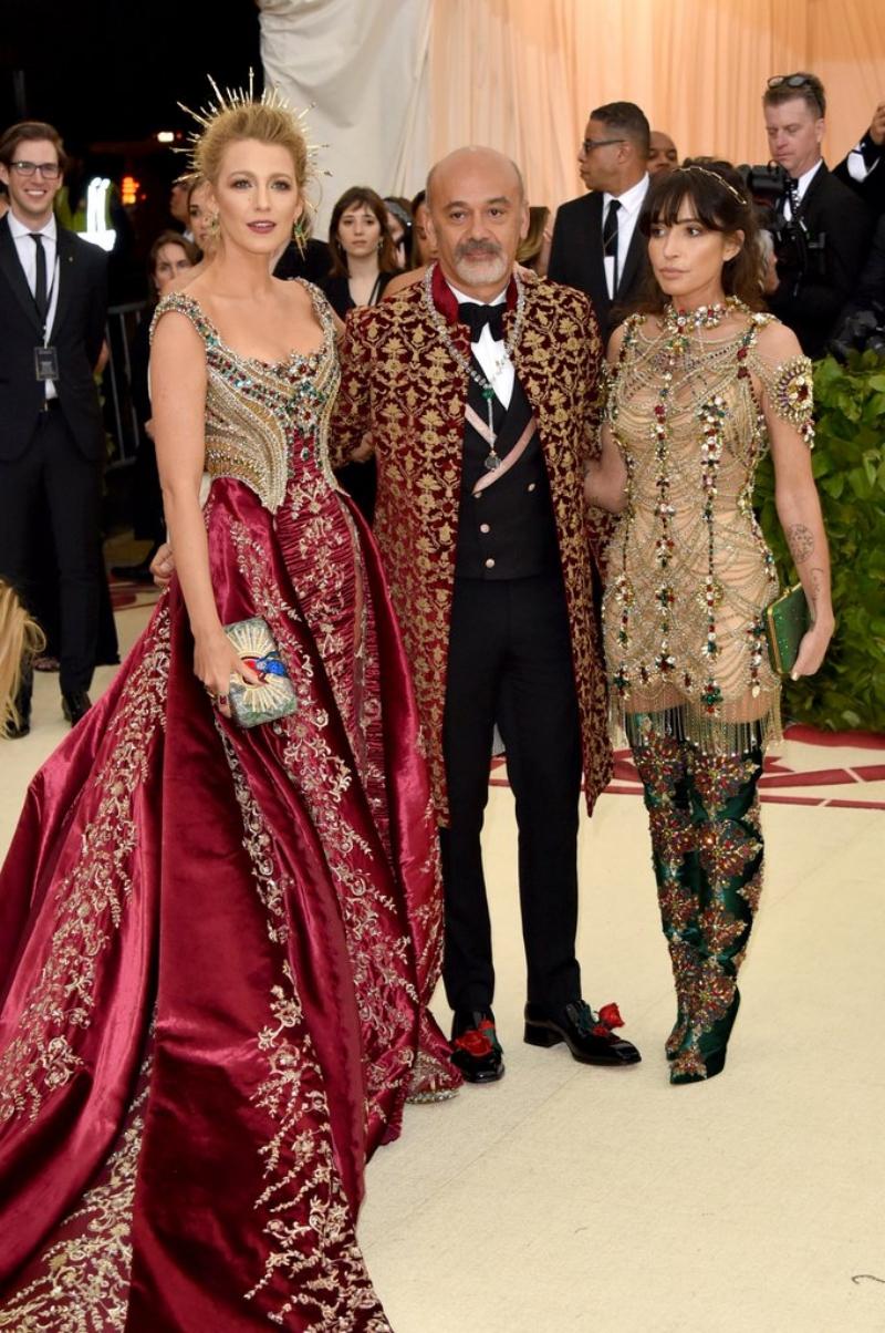"""Cô được """"tháp tùng"""" bởi NTK Christian Louboutin (giữa). Ông cũng thiết kế riêng một đôi boots cho bộ trang phục của Blake Lively, rất tiếc là phải ẩn sau thiết kế đầm lộng lẫy, xa hoa của Versace."""