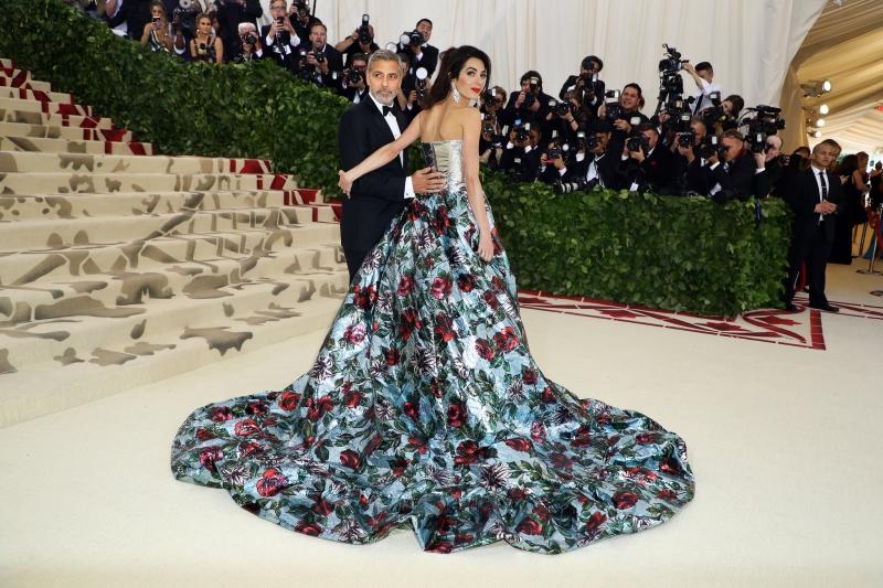 Nữ luật sư Amal Clooney rạng ngời trong thiết kế của Richard Quinn xuất hiện cùng đức lang quân George Clooney. Cô cũng là một trong những chủ tọa khách mời của bữa tiệc MET Gala 2018.
