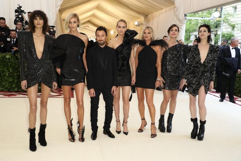 """NTK Anthony Vaccarello (thứ 3 từ trái qua) của thương hiệu Saint Laurent xuất hiện cùng """"đội quân"""" bao gồm: (từ trái qua) người mẫu Mica Arganaraz, người mẫu Anja Rubik, người mẫu kiêm diễn viên đình đám Amber Valletta, siêu mẫu Kate Moss, công nương Monaco Charlotte Casiraghi và nữ diễn viên người Pháp Charlotte Gainsbourg. Tất cả đều mặc trang phục của Saint Laurent."""