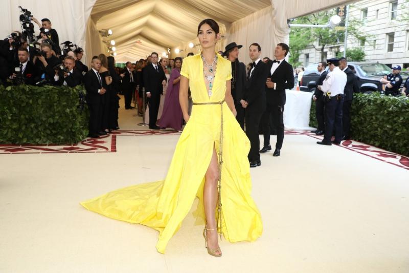 Chân dài Lily Aldrige mặc thiết kế đầm sơ mi với phần đuôi váy dài và tông màu vàng bắt mắt của Ralph Lauren, được tô điểm bởi bộ trang sức bằng ngọc lục bảo và kim cương đắt giá.